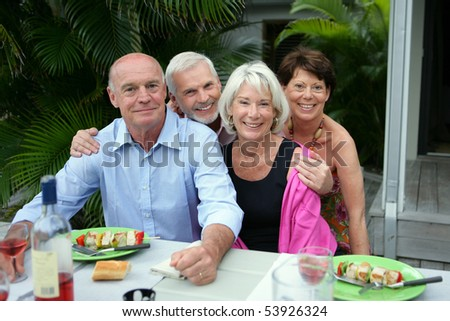 Portrait of a group of smiling seniors during a meal - stock photo