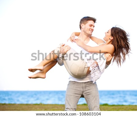 Portrait of a guy carrying his beautiful girlfriend in a windy beach - stock photo