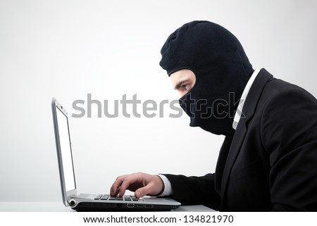 Portrait of a hacker with balaclava against grey background