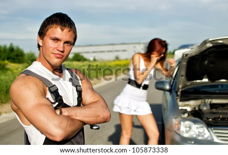 Portrait of a hadsome mechanic with a girl near broken car on a background - stock photo