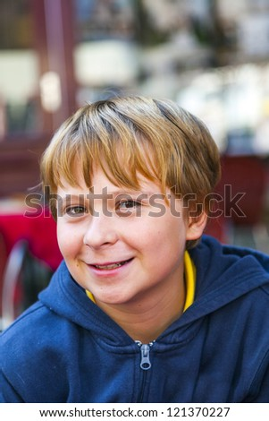 portrait of a hamdsome smiling boy sitting outside