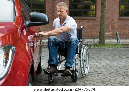 Portrait Of A Handicapped Man Sitting On Wheelchair Opening Door Of A Car - stock photo