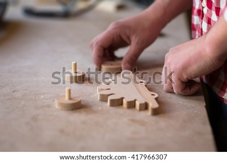 portrait of a hands carpenter planing on composition of  wood element wheel dinosaur toy  at work in the workshop / cabinetmaker's hands using sandpaper on a piece of wood