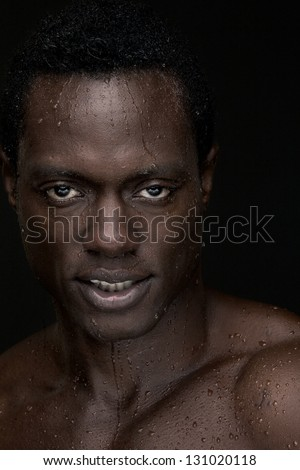 Portrait of a handsome african american man against black background - stock photo