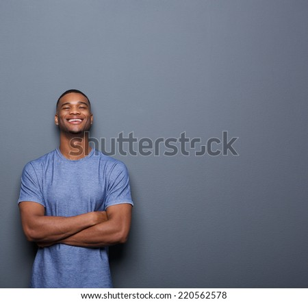 Portrait of a handsome african american man laughing with arms crossed on gray background - stock photo