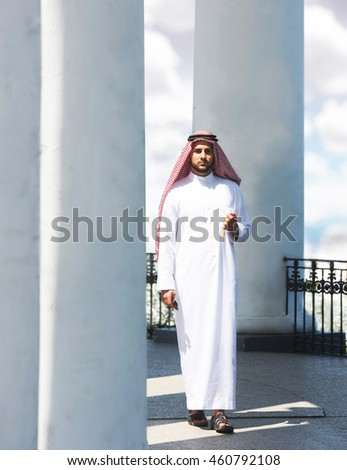 Portrait of a handsome arabian man walking among the columns