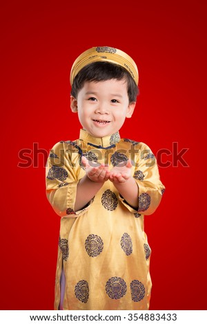 Portrait of a handsome Asian baby boy on traditional festival costume. Happy kid open hands. Cute little Vietnamese boy in ao dai dress smiling. Tet holiday. Lunar New Year