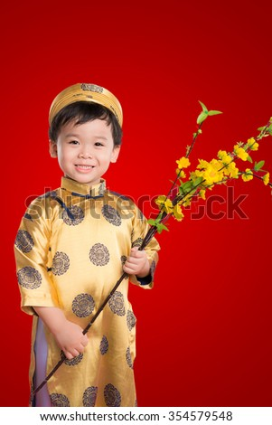 Portrait of a handsome Asian baby boy on traditional festival costume holding Hoa Mai tree (Ochna Integerrima) flower. Cute little Vietnamese boy in ao dai dress smiling. Tet holiday. Lunar New Year. - stock photo