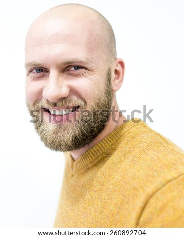 Portrait of a handsome bald young man with beard smiling - stock photo
