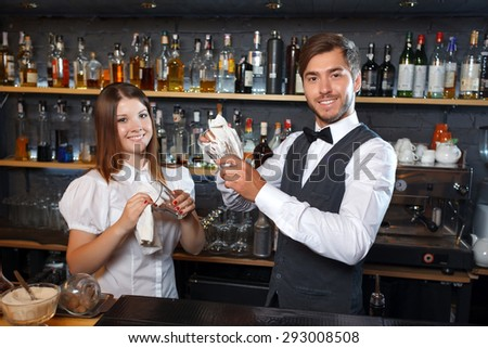 Portrait of a handsome bartender and a pretty waitress standing smiling holding a glass and wiping it standing in the bar, shelves full of bottles with alcohol on the background