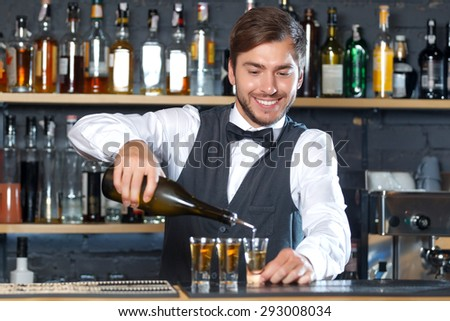 Portrait of a handsome bartender standing at the counter smiling and pouring some shots into small glasses, shelves full of bottles with alcohol on the background - stock photo