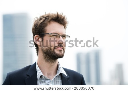 Portrait of a handsome bearded businessman in glasses - stock photo