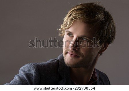 Portrait of a handsome blonde caucasian man wearing a pale purple button shirt with dark grey formal suit jacket. - stock photo