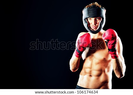 Portrait of a handsome boxer in red gloves and helmet  posing at studio.