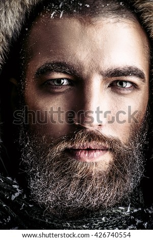 Portrait of a handsome brutal man with beard and mustache dressed in winter clothes, covered with frost.