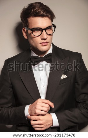 Portrait of a handsome business man looking away while fixing his sleeve. - stock photo