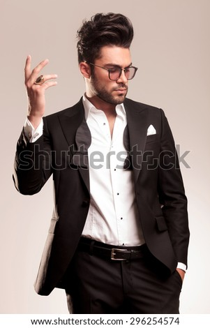 Portrait of a handsome business man looking down while showing his golden ring. He is holding one hand in his pocket. - stock photo