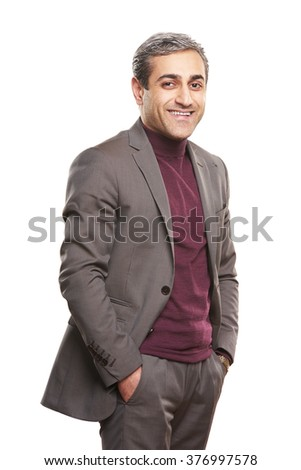 Portrait of a handsome business man standing with his hands in his pockets in front of a gray background