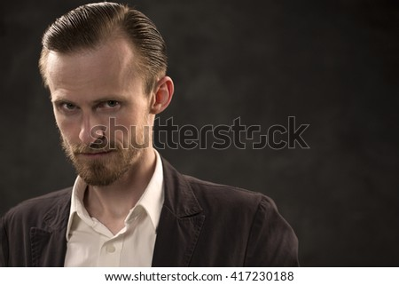 Portrait of a handsome businessman. Angry looking. Low key.