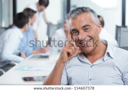 Portrait of a handsome businessman, blurred colleagues in the background  - stock photo
