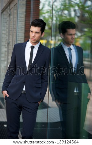 Portrait of a handsome businessman leaning against glass building - stock photo