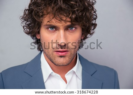 Portrait of a handsome businessman looking at camera over gray background - stock photo