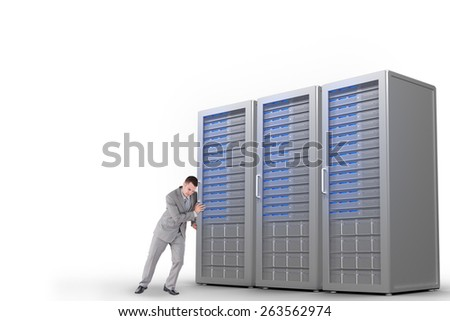 Portrait of a handsome businessman pushing a wall against three digital grey server towers - stock photo