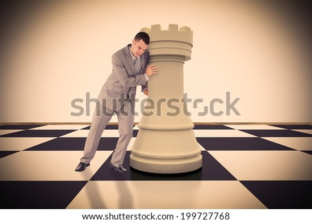 Portrait of a handsome businessman pushing chess piece against white background with vignette - stock photo
