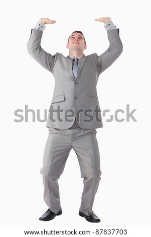 Portrait of a handsome businessman pushing the roof against a white background - stock photo