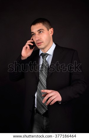 Portrait of a handsome businessman talking on the phone on black background. Handsome man in a suit.