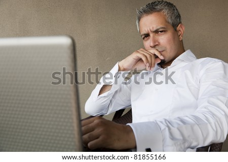portrait of a handsome businessman with grey hair working on the laptop, Indian muslim businessman working. - stock photo