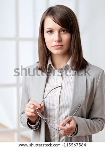 Portrait of a handsome businesswoman handing glasses, isolated on white - stock photo