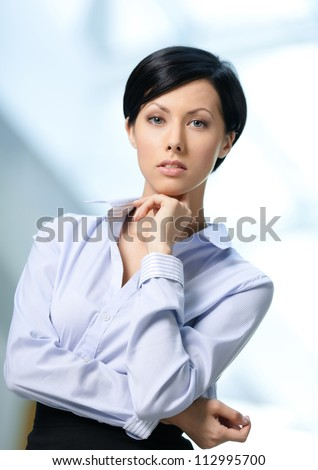 Portrait of a handsome businesswoman wearing white shirt and black skirt at business centre - stock photo