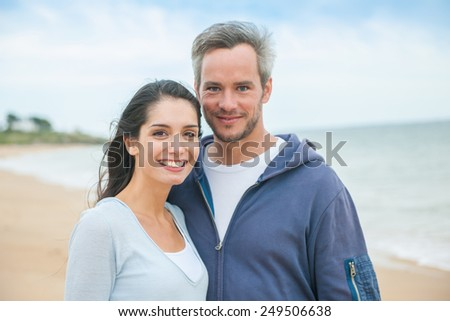 Portrait of a handsome couple at the beach in casual clothes looking at the camera