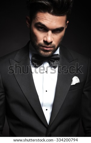 Portrait of a handsome elegant business man looking at the camera with, lifting one eyebrow. - stock photo
