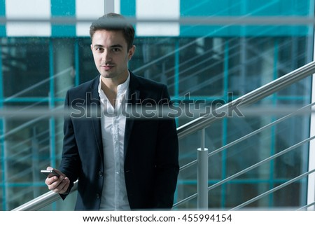 Portrait of a handsome elegant man leaning on a metal banister next to a glass wall