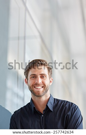 Portrait of a handsome executive looking positively at the camera in a modern setting - stock photo