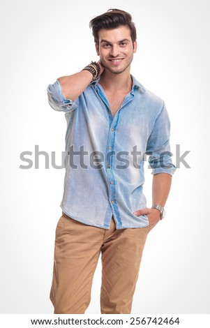 Portrait of a handsome fashion man smiling at the camera while holding one hand to his neck. - stock photo