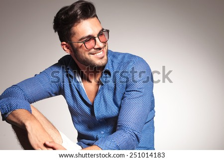 Portrait of a handsome fashion man smiling while looking away from the camera.