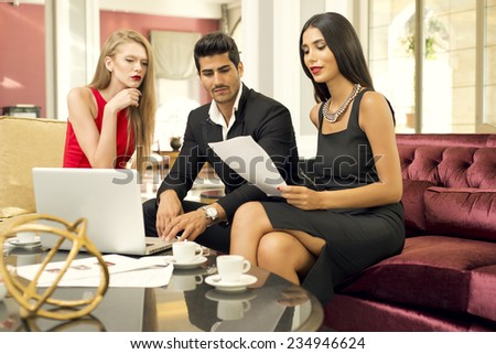 Portrait of a handsome fashionable man with two charming women in a business meeting - stock photo