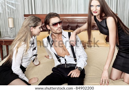 Portrait of a handsome fashionable man with two charming women posing in the interior. - stock photo