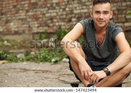 Portrait of a handsome guy who is sitting in the street  - stock photo