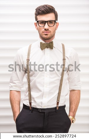Portrait of a handsome guy with glasses, suspenders and bow-tie. - stock photo