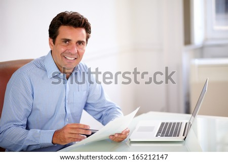 Portrait of a handsome hispanic employee looking at you while holding documents and sitting on office desk