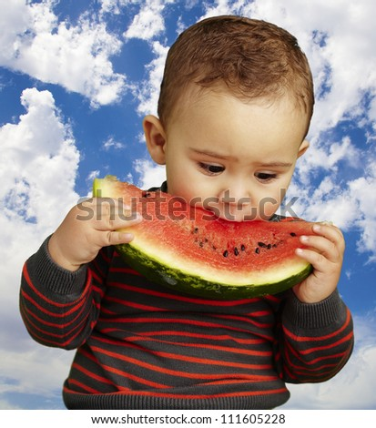 portrait of a handsome kid biting a watermelon against against a