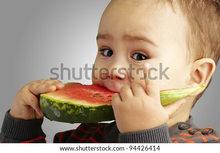 portrait of a handsome kid biting a watermelon over grey background