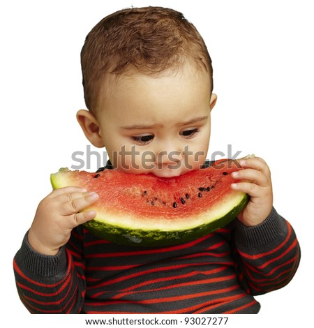 portrait of a handsome kid biting a watermelon over white background