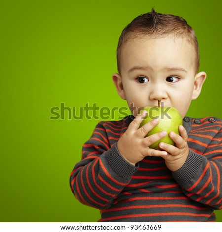 portrait of a handsome kid bitting a green apple over green background - stock photo