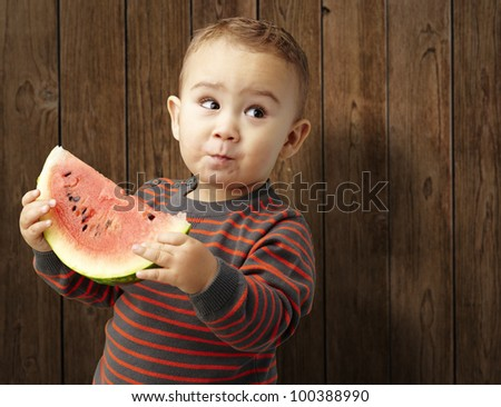 portrait of a handsome kid holding a watermelon and tasting it against a wooden background - stock photo