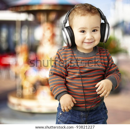 portrait of a handsome kid listening to music and smiling against a carousel background - stock photo